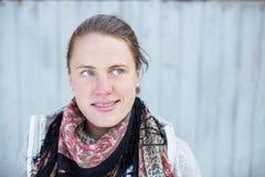 Een portret van een jonge vrouw die aan het recht met een grijze achtergrond kijkt Royalty-vrije Stock Fotografie