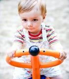 Een portret van een jongen op een schommeling in een speelplaats. Stock Afbeeldingen