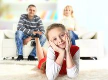 Een portret van een meisje die op de vloer liggen en met haar ouders glimlachen Stock Afbeeldingen