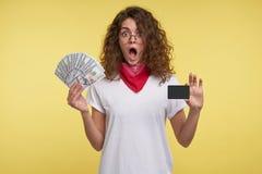 Een portret van gelukkige jonge vrouw die met donkerbruin krullend haar, contant geld en kredietkar in de over geïsoleerde handen royalty-vrije stock fotografie
