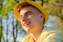 Een portret van een gelukkige tiener buiten, dragend een gele overhemd en een hoed tegen een blauwe hemel, groene boom stock afbeeldingen