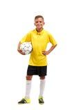 Een portret van gemiddelde lengte van een jonge voetballer in een gele die T-shirtgaten in wapens een bal op een witte achtergron Royalty-vrije Stock Afbeeldingen