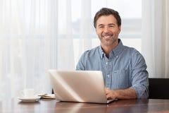 Een portret van een glimlachende gebaarde mens op middelbare leeftijd bij een bureau stock fotografie