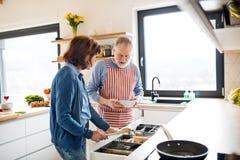 Een portret van hoger paar in liefde binnen thuis, het koken stock foto's