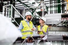 Een portret van een industriële man en vrouweningenieur met klembord in een fabriek, het werken stock foto
