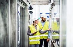 Een portret van een industriële man en vrouweningenieur met tablet in een fabriek, het werken royalty-vrije stock foto