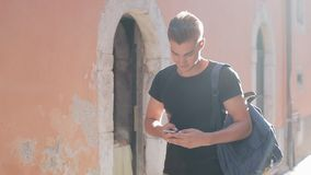 Een portret van een knappe jonge mens het surfen smartphone en het lopen over de stad Zonnige achtergrond Vage achtergrond stock video