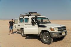 Een portret van een mens dichtbij een auto in de woestijn met zandige en blauwe achtergrond stock foto