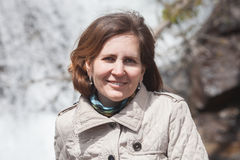 Een portret van middenleeftijdsvrouw tegen waterval Stock Fotografie