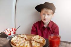Een portret van modieus weinig jongen gekleed in rood overhemd en moderne GLB-zitting bij lijst in de koffie die heerlijke pizza  Royalty-vrije Stock Afbeeldingen