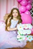Een portret van een mooi meisje in een studio verfraaide vele kleurenballons Stock Foto's