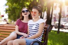 Een portret van twee aantrekkelijke jonge vrienden die rust op houten bank in lokaal park na lange gang hebben De lachende meisje royalty-vrije stock fotografie