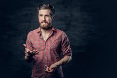 Een positief gebaard mannetje gekleed in een rood vachtoverhemd vertelt een verhaal met handbeweging stock afbeelding
