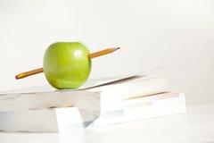 Een potlood door een Appel stock afbeeldingen
