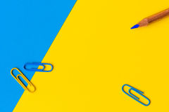 Een potlood en drie paperclips tegen een blauwe en gele backgrou Royalty-vrije Stock Foto