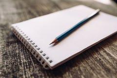 Een potlood en een notitieboekje omhoog stock foto's