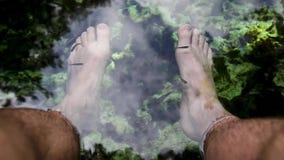 Een POV-schot van voeten in een pool van een cenote in Mexico wenst kleine vissen die rond zwemmen stock footage