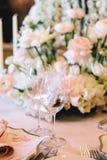 Een prachtig ontworpen huwelijkslijst met bloemensamenstelling van boterbloemen en witte rozen, decoratieve kandelaars royalty-vrije stock afbeelding