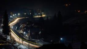 Een prachtig panorama van het dorp van de nachtberg van de Oekraïne met autosporen stock fotografie