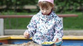 Een pre-school meisjesspelen in de zandbak op de speelplaats stock videobeelden