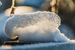 Een pret kleine sneeuwbank van witte sneeuw met gele zonneschijn en bokeh licht bij zonsondergang op een vage achtergrond in een  stock fotografie