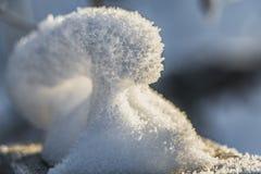 Een pret kleine sneeuwbank van witte sneeuw met gele zonneschijn en bokeh licht bij zonsondergang op een vage achtergrond in een  stock afbeeldingen