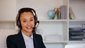 Een pretmeisje met een hoofdtelefoon die de telefoon in het bureau beantwoorden stock footage