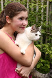 Een pretty girl in pink dress hug siberian cat. Close up photo on green garden fence country summer background Stock Photo