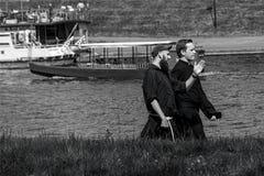 Een Priester en een Monnik lopen door de Wisla Rivier - Krakau 05 2018 stock afbeelding