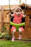 Een prikkelbaar jong meisje die terwijl het spelen op de schommeling lachen royalty-vrije stock afbeelding