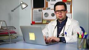 Een privé praktijk arts zit bij het bureau, zijn handen op het laptop toetsenbord stock videobeelden
