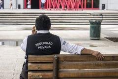 Een privé veiligheidsagent sitted in een bank in een park die in de telefoon spreken stock afbeeldingen