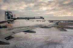 Een proces om anti-icing witte vloeistof het achterdeel van de vleugel van een vliegtuig bij de luchthaven bij zonsopgang te besp royalty-vrije stock afbeelding