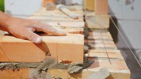 Een professionele arbeider zet de baksteen in het metselwerk stock afbeelding
