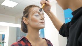 Een professionele grimeur trekt lichaamskunst op het gezicht van het model Het voorbereidingen treffen voor een schoonheidswedstr stock videobeelden