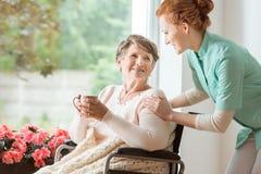 Een professionele huisbewaarder in eenvormig helpend geriatrisch vrouwelijk p stock foto