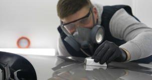 Een professionele mannelijke jongensmeester van keramiek van een auto zet keramiek op een auto stock video