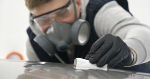 Een professionele mannelijke jongensmeester van keramiek van een auto zet keramiek op een auto stock footage