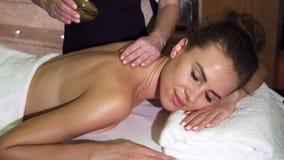Een professionele masseuse giet een mooie klant met olie en masseert haar royalty-vrije stock afbeeldingen