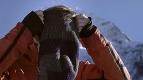 Een professionele ruiter zet op een wollen skimasker of balaclava op zijn hoofd Het worden klaar te skien of snowboard enjoys stock video