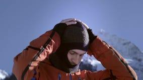 Een professionele ruiter zet op een wollen skimasker of balaclava op zijn hoofd Het worden klaar te skien of snowboard enjoys stock videobeelden