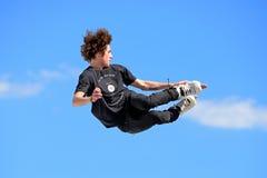 Een professionele schaatser bij het Gealigneerde schaatsen springt de concurrentie Stock Foto