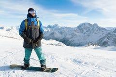 Een professionele snowboarder bevindt zich met zijn snowboard Close-up Portret van freerider Stock Foto