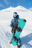Een professionele snowboarder bevindt zich met zijn snowboard tegen de blauwe hemel Stock Afbeeldingen