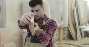 Een professionele timmerman raakt de raad van de spaanplaat in de houtbewerkingsindustrie stock video