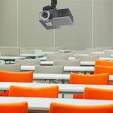 Een projector over lege zetels met lijsten in een conferentiezaal Stock Fotografie