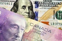Een purpere Canadese tien dollarrekening met een Amerikaanse honderd dollarrekening stock fotografie