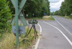 Een radarval bij de kant van de weg vóór een spoorwegovergang stock afbeelding