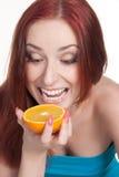 Een redhead vrouw met een sinaasappel Stock Foto's