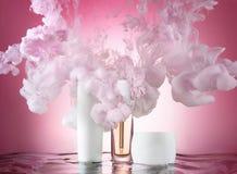 Een reeks bevochtigende schoonheidsmiddelen in een watergolf met roze verf rond clubs, roze achtergrond Stock Foto